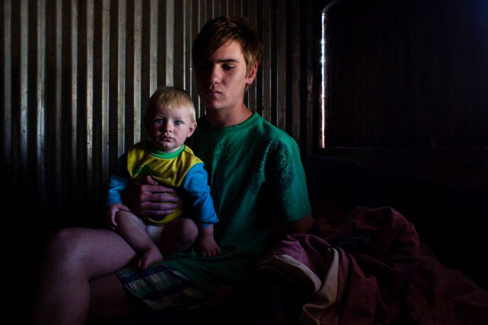 "Rudolph Mulder, 16 year old boy holding neighbor's child. Photograph by Sipho Mpongo from the ""Twenty Journey Project"" - www.twentyjourney.com"