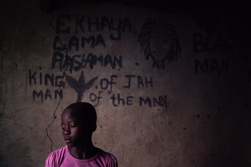 "Saneliswa Mthebu, 8 year old girl in her uncle's room. Photograph by Sipho Mpongo from the ""Twenty Journey Project"" - www.twentyjourney.com"